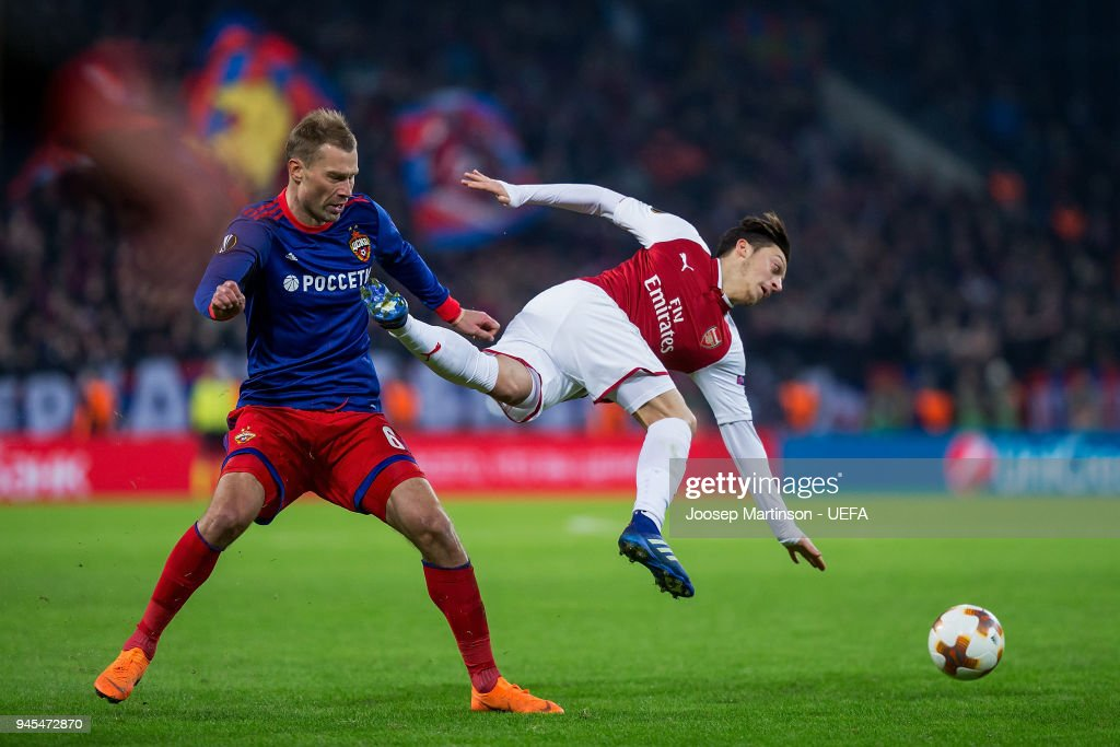 Aleksei Berezutski of CSKA Moskva tackles Mesut Ozil of Arsenal during the UEFA Europa League quarter final leg two match between CSKA Moskva and Arsenal FC at CSKA Arena on April 12, 2018 in Moscow, Russia.