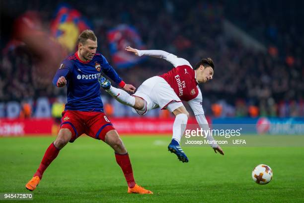 Aleksei Berezutski of CSKA Moskva tackles Mesut Ozil of Arsenal during the UEFA Europa League quarter final leg two match between CSKA Moskva and...