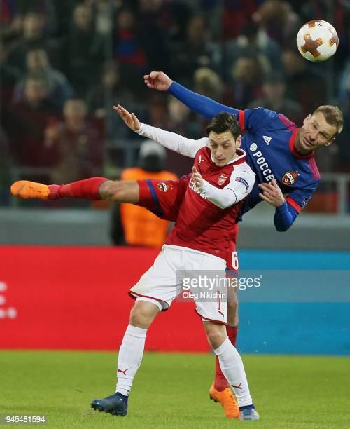 Aleksei Berezutski of PFC CSKA Moskva vies for the ball with Mesut Ozil of Arsenal FC during the UEFA Europa League quarter final leg two match...