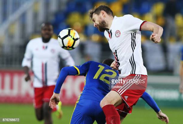 Aleksei Ionov of FC Rostov RostovonDon vies for the ball with Mikhail Sivakow of FC Amkar Perm during the Russian Premier League match between FC...
