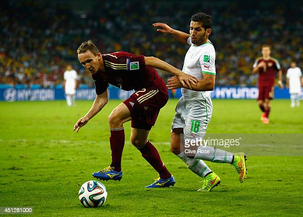 Aleksei Kozlov of Russia challenges Abdelmoumene Djabou of Algeria during the 2014 FIFA World Cup Brazil Group H match between Algeria and Russia at...