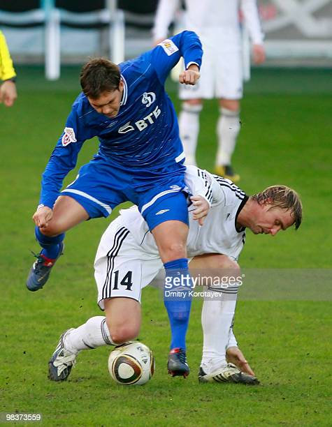 Aleksei Rebko of FC Dinamo Moskva battles for the ball with Sergei Kornilenko of FC Tom Tomsk during the Russian Football League Championship match...
