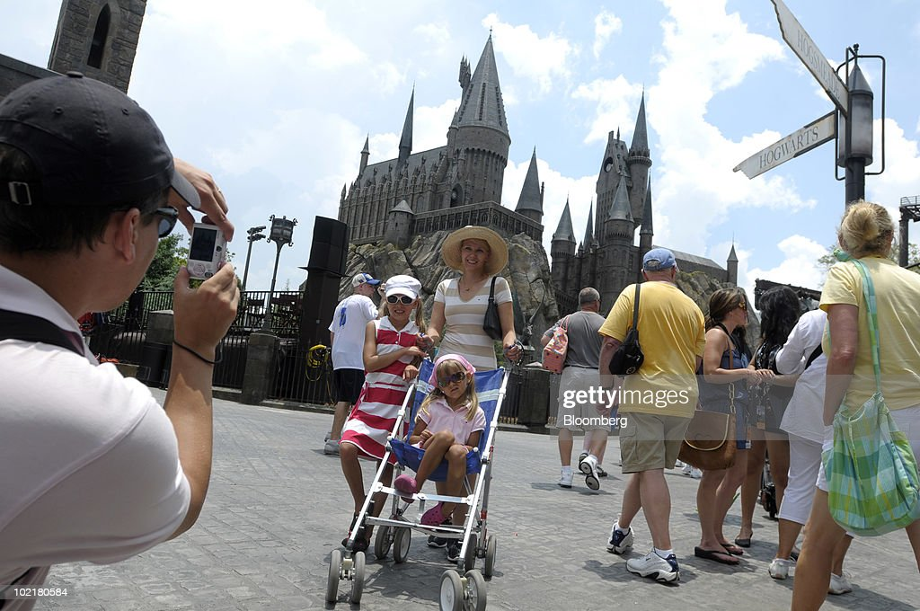 Aleksi Heino, left, of Finland, photographs his wife Anne and daughters Jasmin, 9, left, and Janina, 6, in front of Hogwarts castle at the Universal Studios Wizarding World of Harry Potter theme park in Orlando, Florida, U.S., on Thursday, June 17, 2010. Universal reportedly spent $265 million building the theme park, based on a Securities & Exchange Commission filing. Photographer: Phelan M. Ebenhack/Bloomberg via Getty Images