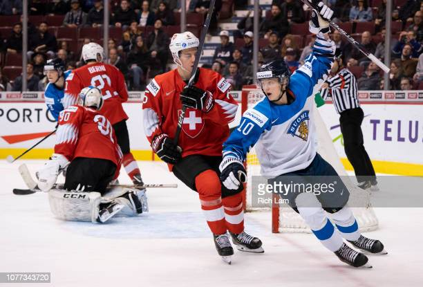 Aleksi Heponiemi of Finland celebrates teammate Aarne Talvitie's goal as Marco Lehmann of Switzerland skates past in Semifinals hockey action of the...