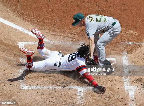 Alen Hanson of the Chicago White Sox is tagged out at the plate after a wild pitch by starting pitcher Sonny Gray of the Oakland Athletics in the 1st...