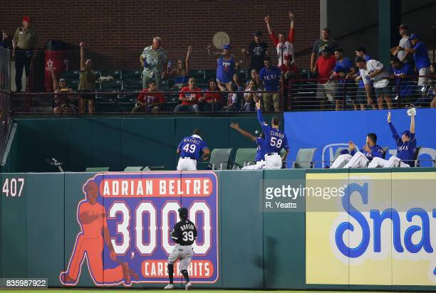 Alen Hanson of the Chicago White Sox looks on as fans cheep as Jhan Marinez of the Texas Rangers and Alex Claudio avoid a home run ball hit in the...