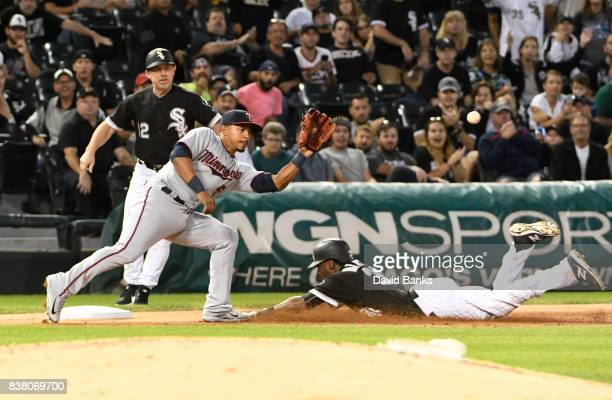 Alen Hanson of the Chicago White Sox slides safely into third base with a triple as Eduardo Escobar of the Minnesota Twins takes the throw during the...