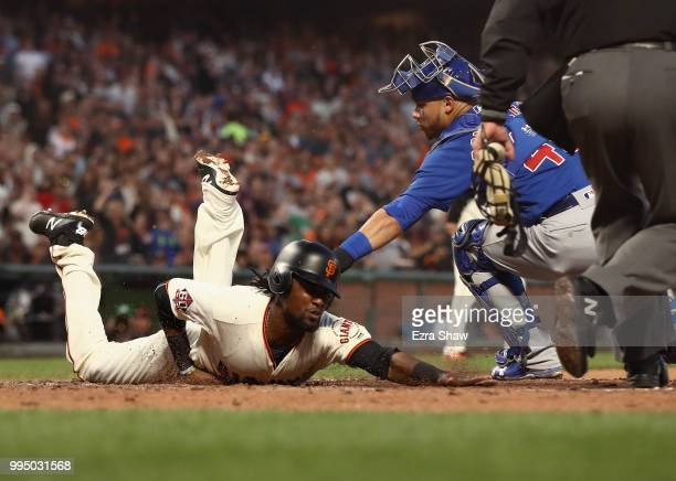 Alen Hanson of the San Francisco Giants beats the tag of Willson Contreras of the Chicago Cubs to score after a failed pick off attempt in the fifth...