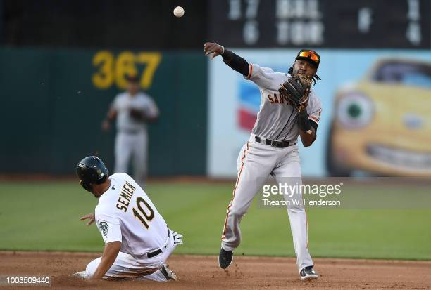 Alen Hanson of the San Francisco Giants completes the doubleplay throwing over the top of Marcus Semien of the Oakland Athletics in the bottom of the...