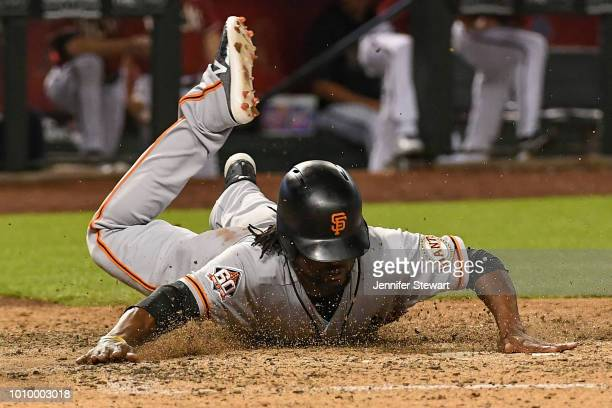 Alen Hanson of the San Francisco Giants safely slides into home plate to score against the Arizona Diamondbacks in the eighth inning of the MLB game...