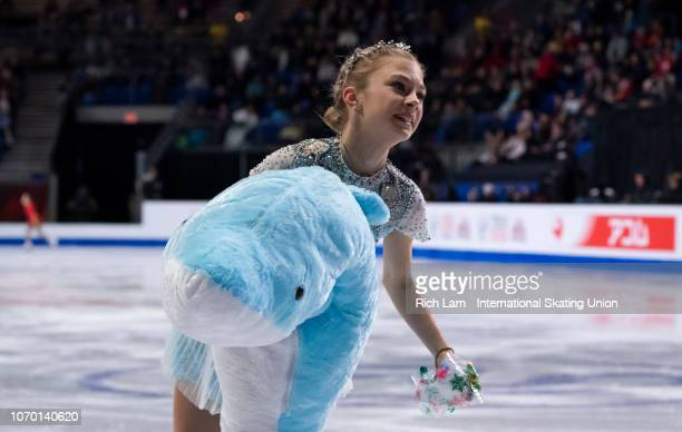 Alena Kanysheva of Russia skates off with a stuffed shark after competing in the Free Skate portion of the Junior Ladies Championships on December...