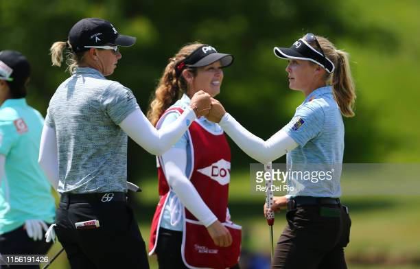 Alena Sharp of Canada celebrates with Brooke Henderson of Canada on the ninth hole after their first round of the Dow Great Lakes Bay Invitational at...