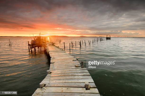 alentejo amazing landscape. sunset landscape of artisanal fishing boats in the old wooden pier. carrasqueira is a tourist destination for visitors to the coast of alentejo near lisbon. - comporta portugal stock photos and pictures