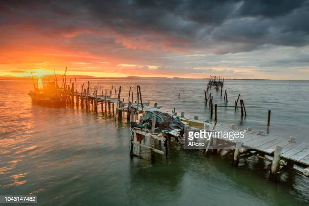 alentejo, portugal. sunset landscape of artisanal fishing boats in the old wooden pier - comporta portugal stock photos and pictures