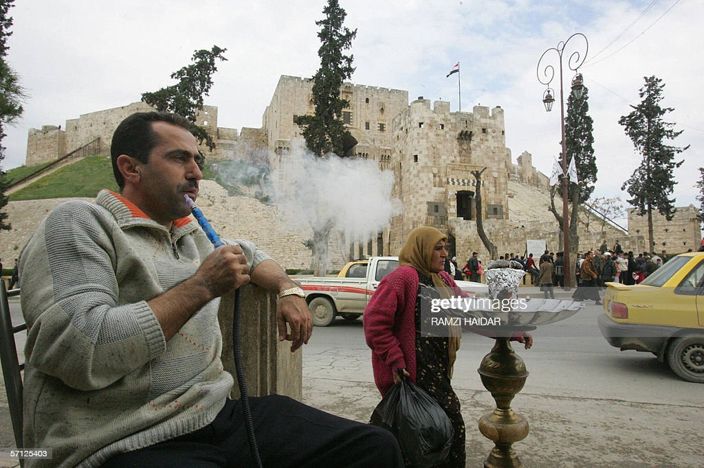 A man smokes his water pipe in front of the Aleppo citadel, an Islamic landmark and the most prominent historic architectural site in Aleppo, as the city is inaugurated today as the Arab world's Islamic cultural capital, 18 March 2006. Syrian Culture Minister Riad Nassan Agha said yesterday Aleppo was chosen by the Organization of the Islamic Conference (OIC) because of its role as the 'main point of passage between East and West.'