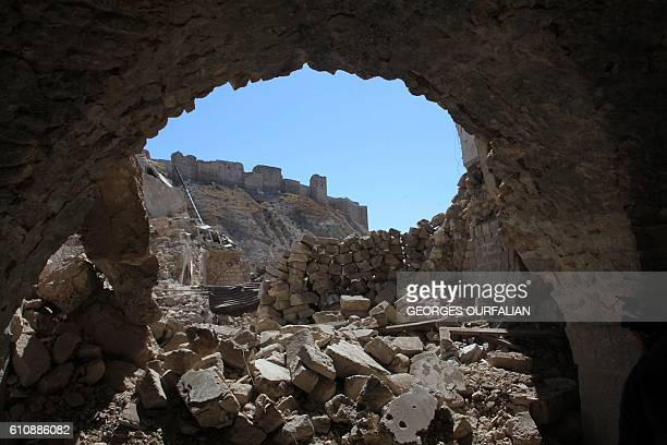 Aleppo's citadel is seen through destruction in this picture taken on September 28 2016 in the Farafira district northwest of the city's historic...
