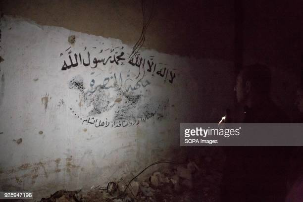 Aleppo's representative for reconciliation Fadi Ahmad Ismail points out graffiti he says proves Al Nusra controlled Bustan al Qasr neighbourhood...