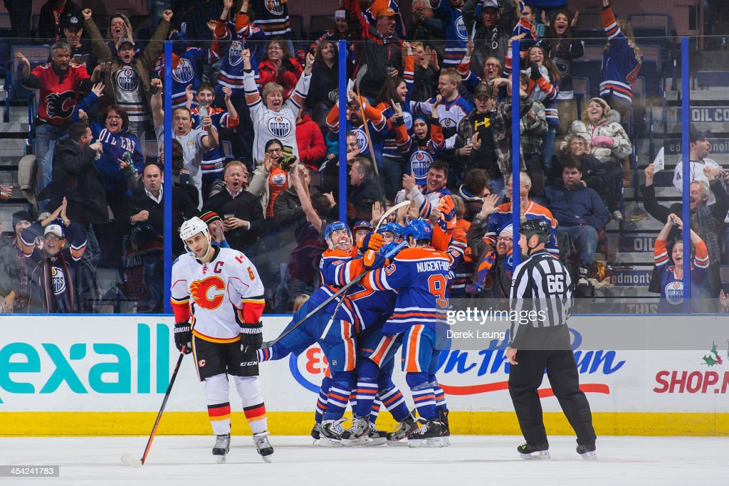 Ales Hemsky #83, David Perron #57, Taylor Hall #4, and Ryan Nugent-Hopkins #93 of the Edmonton Oilers celebrate the game-tying goal by Taylor Hall #4 to force overtime against the Calgary Flames during an NHL game at Rexall Place on December 7, 2013 in Edmonton, Alberta, Canada. The Flames defeated the Oilers 2-1 in overtime.