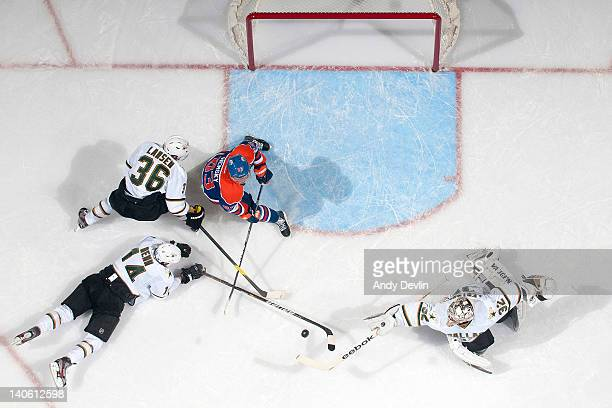 Ales Hemsky of the Edmonton Oilers and Kari Lehtonen of the Dallas Stars reach for the loose puck at Rexall Place on March 2 2012 in Edmonton Alberta...