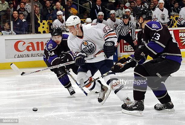 Ales Hemsky of the Edmonton Oilers pushes the puck up the ice against Alexander Frolov and Dustin Brown of the Los Angeles Kings on January 26 2006...