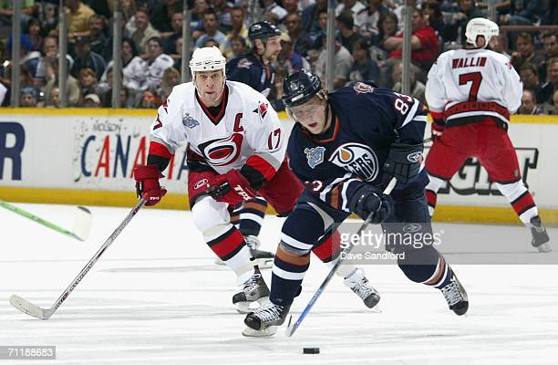 Ales Hemsky of the Edmonton Oilers skates with the puck under pressure from Rod Brind'Amour of the Carolina Hurricanes during game four of the 2006...