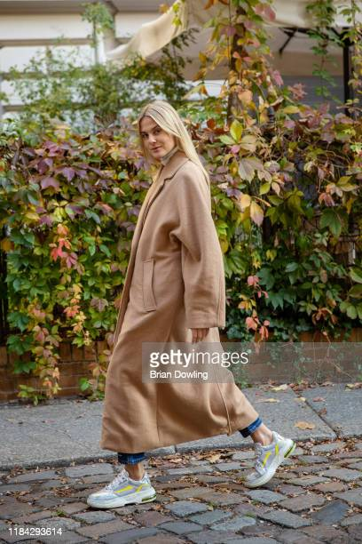 Alessa Winter is seen wearing a cream colored turtleneck and oversized camel wool coat by Weekday, denim jeans by Closed and sneakers by Premiata on...