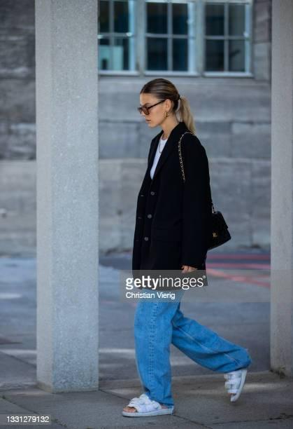 Alessa Winter is seen wearing black blazer, white top, sunglasses, Chanel bag, denim jeans, white sandon July 28, 2021 in Berlin, Germany.