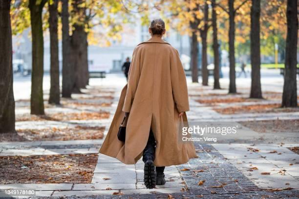 Alessa Winter is seen wearing black boots Miu Miu, Lala Berlin leather pants, Edited jumper, beige Weekday coat, Prada bag and sunglasses on October...