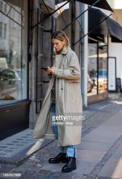 Alessa Winter seen wearing denim jeans, trench coat in beige, black boots Copenhagen Studios on August 12, 2021 in Copenhagen, Denmark.