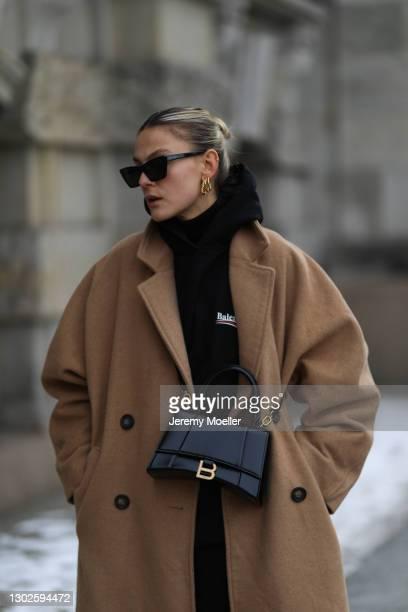 Alessa Winter wearing Balenciaga hoodie and black bag, Weekday beige coat, Saint Laurent shades and The Pangaia black joggingpants on February 15,...