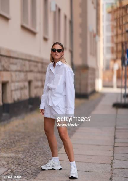 Alessa Winter wearing black Balenciaga leather bag, white The Frankie Shop set, white Nubikk sneakers and black Ochre Lane shades on June 27, 2021 in...