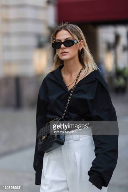 Alessa Winter wearing black Prada shades, black shirt, white pants and black Chanel leather flap bag on July 12, 2021 in Berlin, Germany.