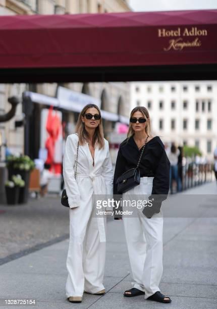 Alessa Winter wearing black Prada shades, black shirt, white pants, black slippers and black Chanel leather flap bag and Anna Winter wearing black...