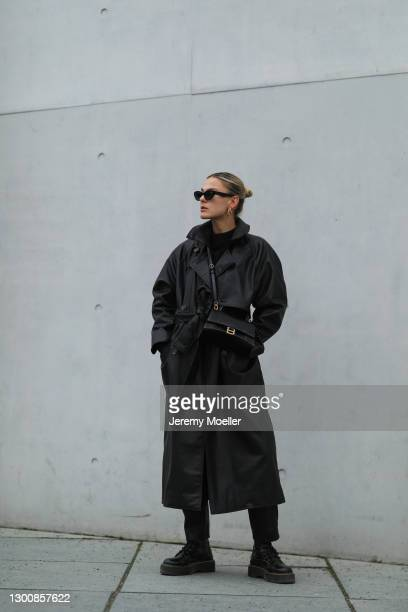 Alessa Winter wearing black shades, Zara black coat, Balenciaga leather bag and Dr. Martens boots on February 05, 2021 in Berlin, Germany.