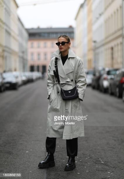 Alessa Winter wearing Iro beige coat, black Prada boots and bag, black shades and Zara pants on February 05, 2021 in Berlin, Germany.