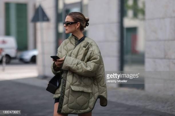 Alessa Winter wearing Prada black shades, the Frankie Shop olive jacket and Balenciaga black bag on August 03, 2021 in Berlin, Germany.