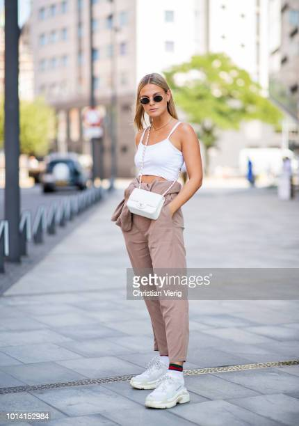Alessa Winter wearing white cropped top white Chanel bag beige pants asymmetrical sneakers seen outside Designers Remix during the Copenhagen Fashion...