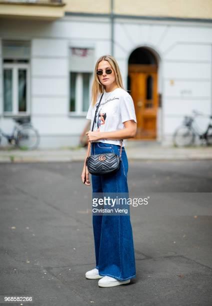 Alessa Winter wearing wide leg Zara denim jeans black Gucci bag white Nubik sneakers Fiorucci tshirt with print Ray Ban sunglasses on June 6 2018 in...