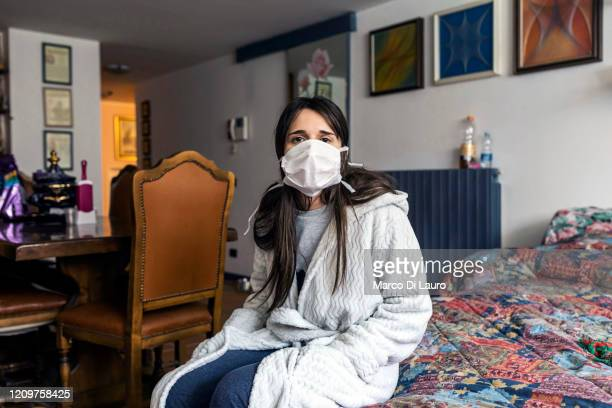 Alessandra 25yearsold a COVID19 positive patient sits on her bed at her family house as the crew of an Italian Red Cross ambulance perform an...