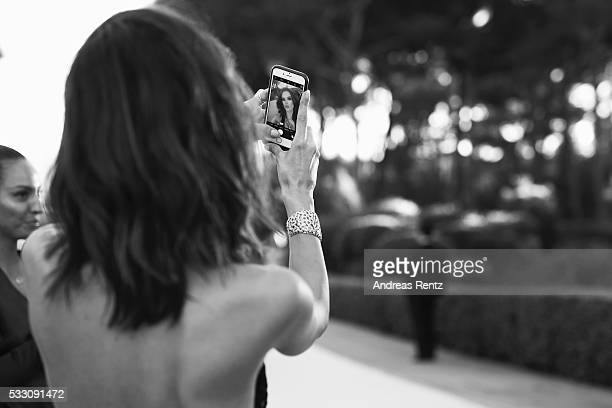 Alessandra Ambrosio uses her smartphone at the amfAR's 23rd Cinema Against AIDS Gala at Hotel du CapEdenRoc on May 19 2016 in Cap d'Antibes France