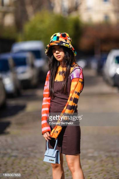 Alessandra Huynh @atiashuynh wears a fluffy colorful bob hat from Asos, a tie and dye multicolor top from Asos with printed patterns, a brown short...