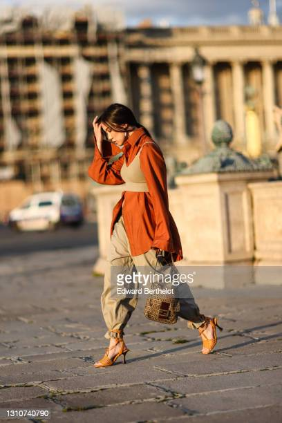 Alessandra Huynh @atiashuynh wears an orange oversized shirt with flared sleeves, a cropped tank top, beige pants, a brown monogram printed Fendi...