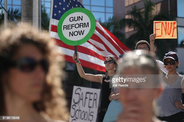 Alessandra Mondolfi holds a sign that reads 'gun reform now' as she joins other people after a school shooting that killed 17 to protest against guns...