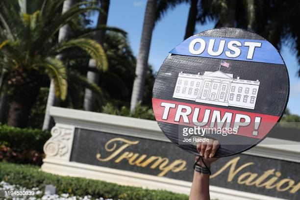 Alessandra Mondolfi holds a sign that reads 'Oust Trump' as she joins with other protesters outside of the Trump National Doral golf resort urging...