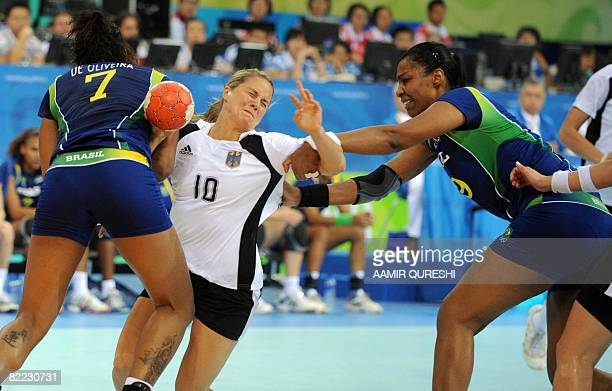 Alessandra Oliverira and Juan Santos of Brazil vie with Anna Loerper of Germany during their 2008 Olympics Games Handball women's match on August 9...