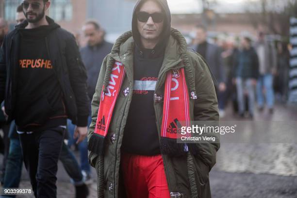 Alessandro Altomare wearing red Adidas scarf olive parak red track suit pants is seen during the 93 Pitti Immagine Uomo at Fortezza Da Basso on...