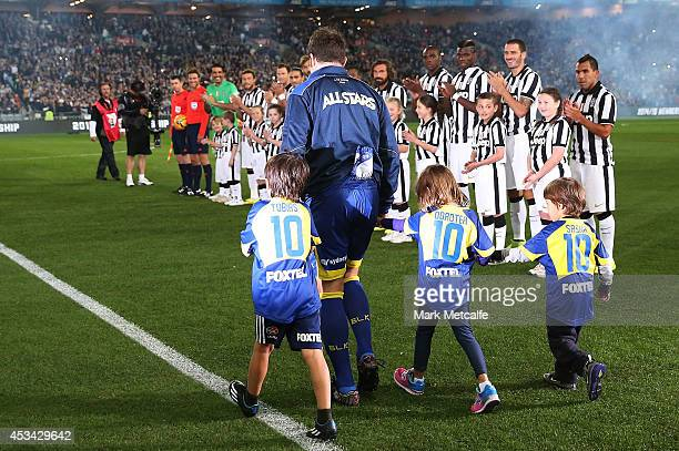 Alessandro Del Piero of the All Stars walks onto the field with his children and is appluaded by the Juventus team during the match between the...