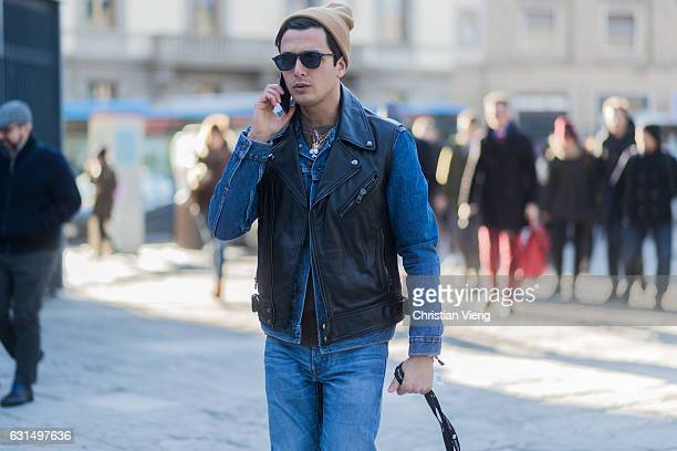 Alessandro Enriquez is wearing a leather vest denim jacket denim jeans sunglasses beanie while talking on the phone on January 11 2017 in Florence...