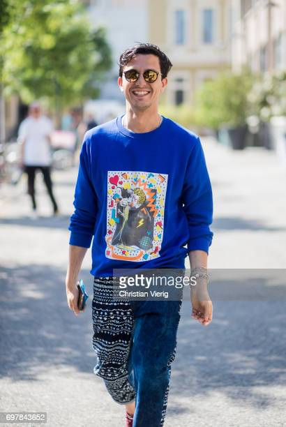 Alessandro Enriquez wearing a blue sweater with print denim jeans is seen outside GCDS during Milan Men's Fashion Week Spring/Summer 2018 on June 19...