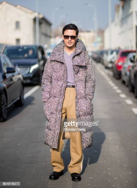 Alessandro Enriquez wearing down feather coat beige pants is seen outside DSquared2 during Milan Men's Fashion Week Fall/Winter 2018/19 on January 14...